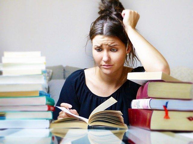 žena zavalená učebnicemi nestíhající svůj harmonogram.jpg